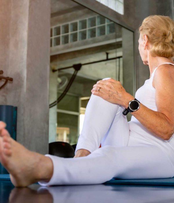 senior-woman-caucasian-doing-yoga-exercise-fitness-gym