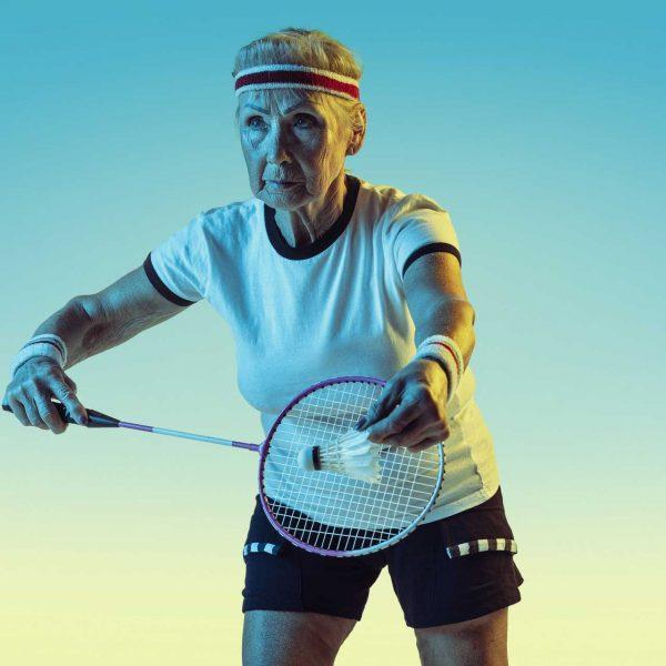 senior-woman-playing-badminton-sportwear-gradient-wall-neon-light