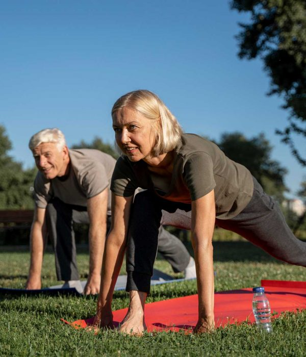 side-view-older-couple-practicing-yoga-outdoors